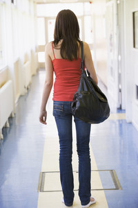 Rear view of female college student in university corridor