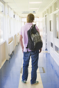 Rear view of male college student standing in university corridor