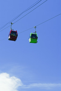 Red and Green cable car lift on blue sky at vietnam