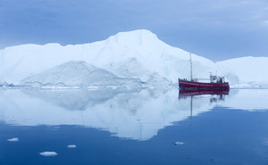 Red boat set against a towering iceberg