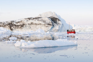 Red boat traveling past a dirt-streaked iceberg and ice floe at dawn