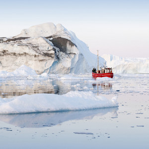Red boat traveling past a dirt-streaked iceberg and ice floes at dawn
