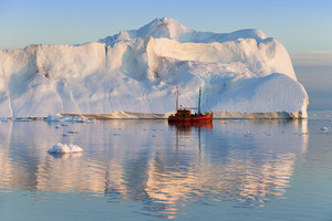 Red boat traveling past a sunlit iceberg in icy waters