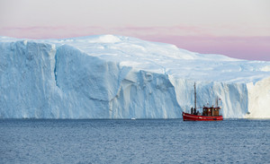 Red boat traveling past a towering iceberg in soft morning light