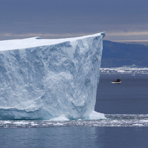 Red boat traveling past a towering iceberg under a grey sky