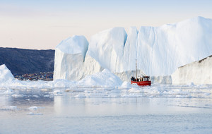 Red boat traveling past an iceberg along the coast