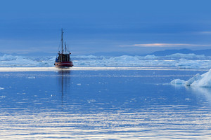 Red boat traveling past an iceberg and ice floe along the coast at dusk