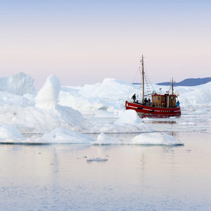 Red boat traveling past an iceberg and ice floe at dawn along the coast