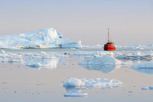 Red boat traveling past an iceberg and ice floe at dawn