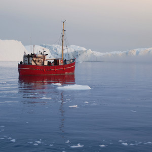 Red boat traveling past an iceberg and ice floe at dusk