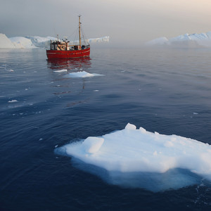 Red boat traveling past an iceberg and ice floe on a foggy day