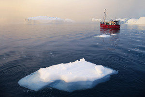 Red boat traveling past an iceberg at a foggy dusk