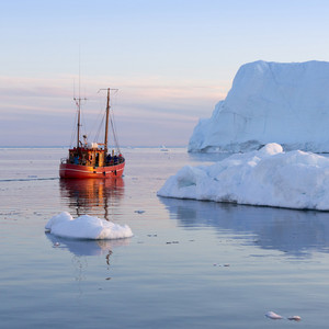 Red boat traveling past an iceberg at dusk