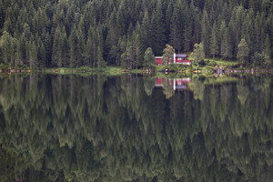 Red cottage and forest reflected in a still lake