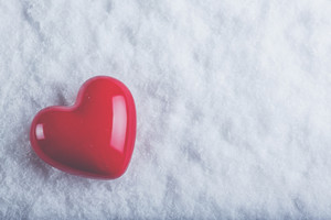Red glossy heart on a frosty white snow winter background
