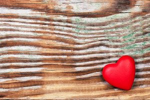 Red heart on grunge wooden background