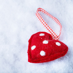 Red toy suave heart on a frosty white snow winter background