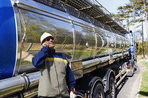 refinery worker filling large fuel truck