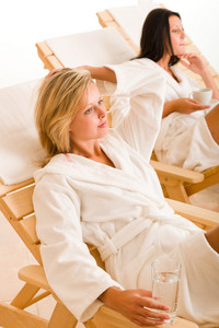 Relax luxury spa beauty women enjoy refreshments lying on sun-beds