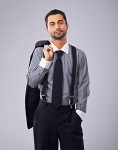 Relaxed businessman holding his coat looking at you