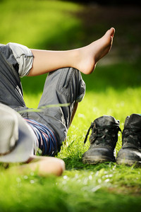 Relaxed kid resting on summer park grass meadow wearing father's big shoes
