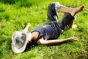 Relaxed kid resting on summer park grass meadow