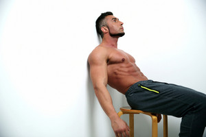 Relaxed muscular man sitting on the chair