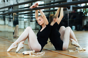 Relaxed woman sitting on the floor in ballet class