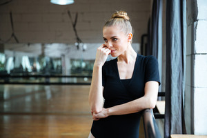 Relaxed woman standing in ballet class and looking away