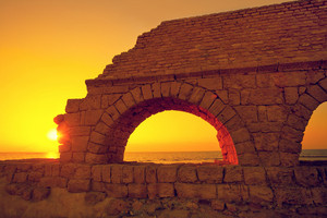 Remains of the ancient Roman aqueduct in ancient city Caesarea at sunset