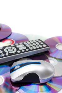 Remote control and computer mouse over a bed of dvd disks isolated over white.