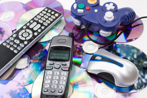 Remote control wireless computer mouse cordless telephone and video game controller over a bed of dvd disks isolated over white.