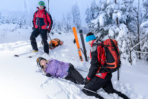 Rescue ski patrol help injured woman skier lying in snow