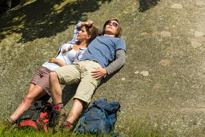 Resting Caucasian couple enjoying sunshine on rock backpack