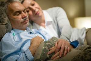 Retired ill man and caring wife sleeping together holding hands