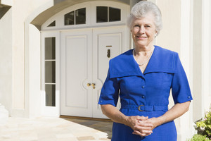Retired woman standing in front of house