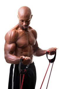 Ripped body builder working out his biceps using a resistance band.