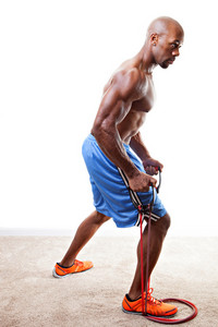 Ripped body builder working out  using a resistance band.