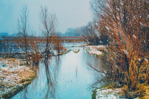 River in snowy weather in evening
