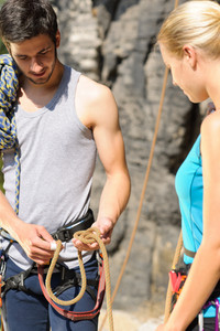 Rock climbing active young man showing mountaineer woman rope knot