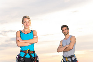 Rock climbing active young mountaineers reach top at sunset