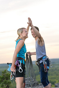 Rock climbing cheerful active young mountaineers reach top at sunset