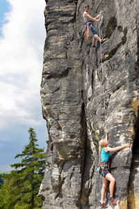 Rock climbing male instructor hold rope blond woman hanging