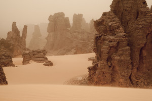 Rock formations in a sandy desert under thick fog