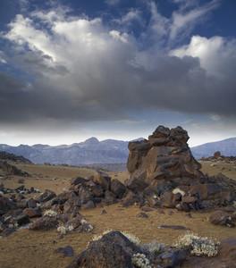 Rocks on a barren landscape under a cloudy sky