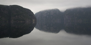 Rocky cliffs reflected in a foggy lake