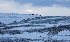 Rocky hillside covered in snow at dawn