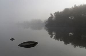 Rocky lake and shore in thick fog