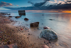 Rocky sea shore with world war II military bunker. Long exposure photo. Baltic sea shore.