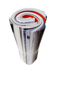 Rolled up magazines isolated over white. Shallow depth of field.